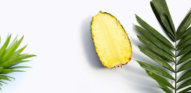 Ananas frais sur des feuilles de palmiers tropicaux sur fond blanc. espace de copie