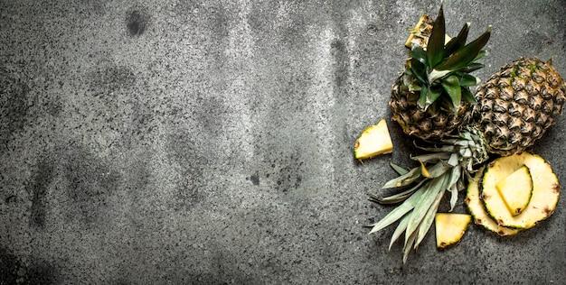Ananas frais mûrs sur table rustique.