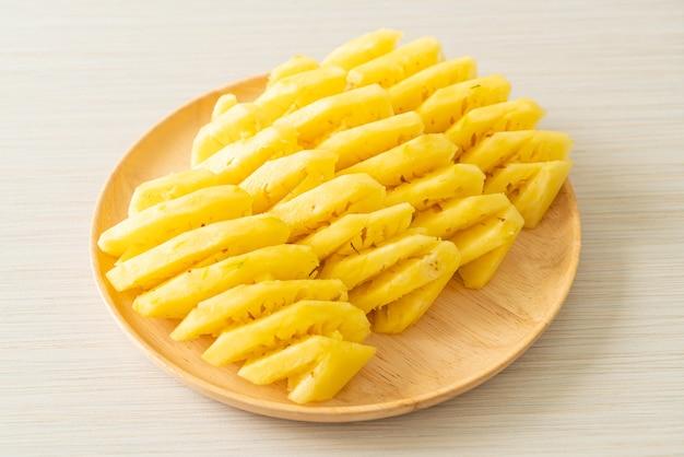 Ananas frais tranché sur plaque de bois