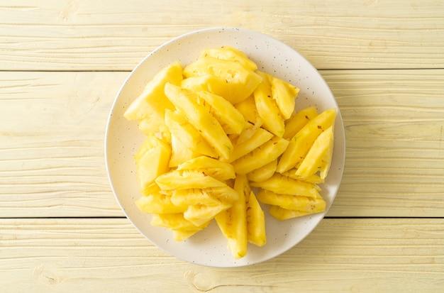 Ananas frais tranchés sur plaque blanche