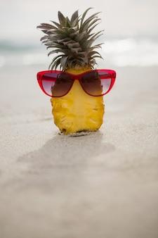 Ananas halved et un sunglass conservés sur le sable