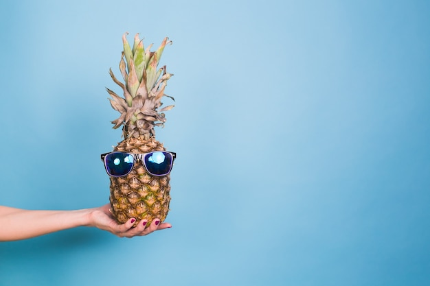 Ananas hipster à la mode. couleur d'été lumineuse, accessoires. fruits tropicaux sur fond bleu avec espace de copie