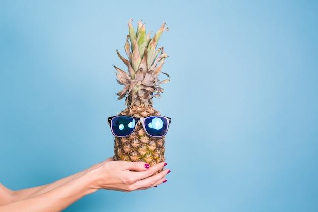 Ananas hipster à la mode. couleur d'été lumineuse, accessoires. fruits tropicaux sur fond bleu avec fond