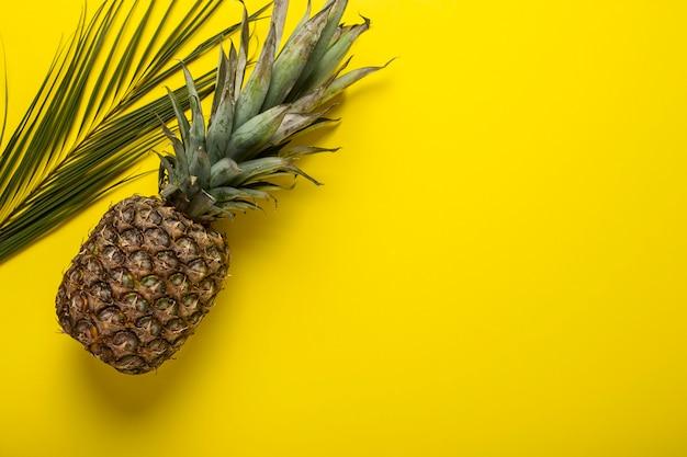 Ananas jaune entier frais et mûrs et palmiers lsit. vue de dessus, mise à plat