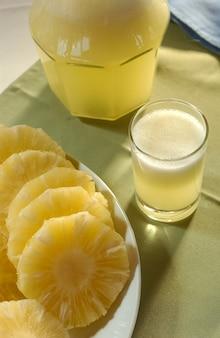 Ananas. jus et fruits coupés sur la table.