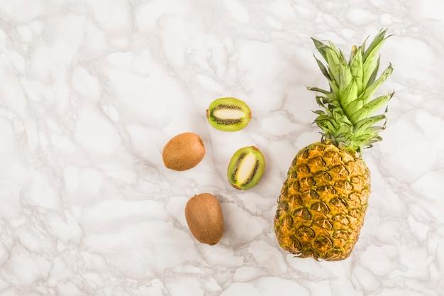 Ananas et kiwi vue de dessus sur marbre