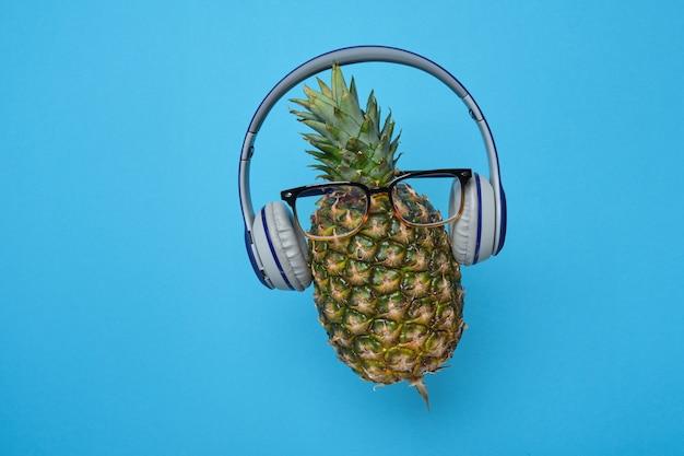 Ananas en lévitation avec lunettes et écouteurs sur fond bleu avec espace de copie