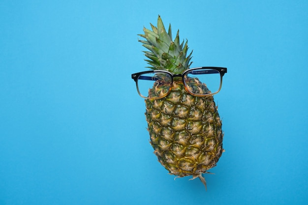 Ananas en lévitation avec des lunettes sur fond bleu avec espace pour copie