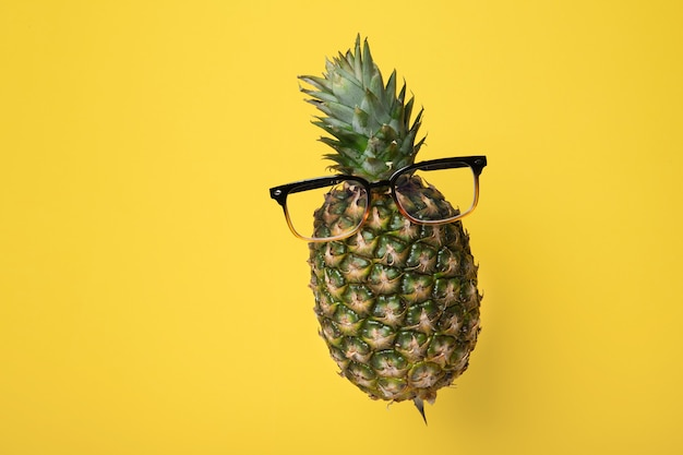 Ananas en lévitation avec des lunettes sur fond jaune avec espace de copie