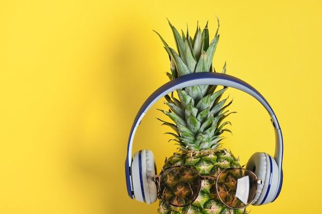 Ananas avec lunettes de soleil et casque sur fond jaune