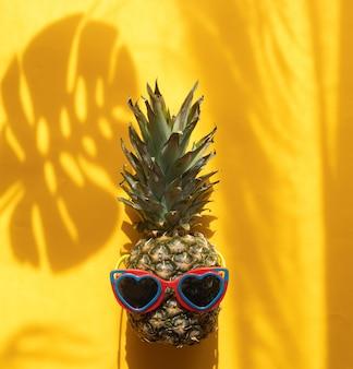 Ananas avec des lunettes de soleil en forme de coeur sur fond jaune avec des ombres de feuilles tropicales