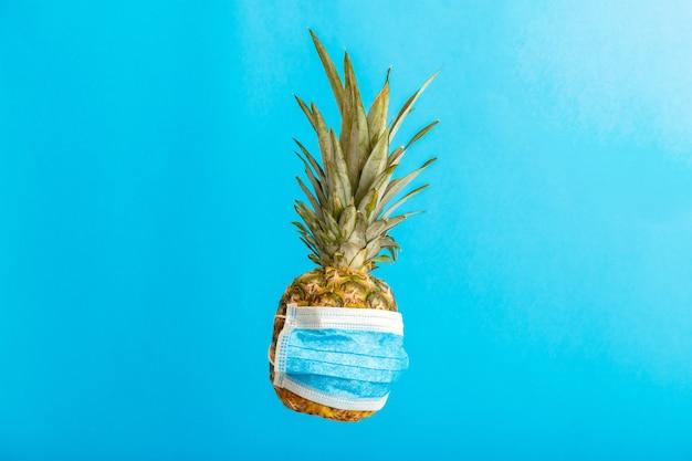 Ananas en masque médical sur fond bleu de couleur. fruit d'ananas dans un masque facial pendant le verrouillage de covid. concept de voyage et de vacances de fond d'été ananas en lévitation. photo de haute qualité
