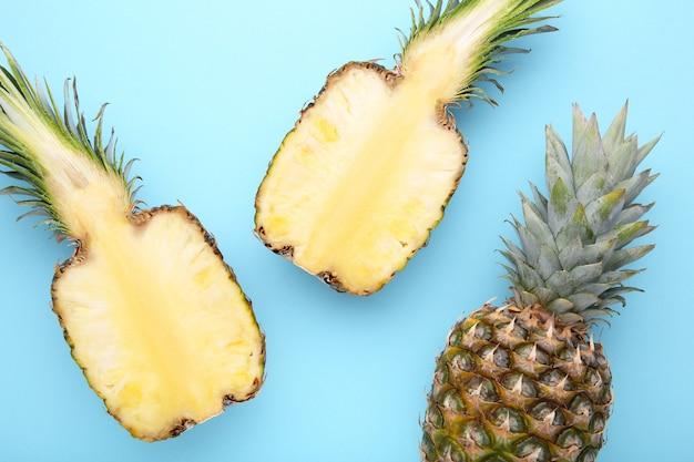 Ananas et moitié d'ananas sur fond bleu