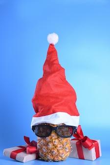 Ananas mûr, ananas avec des lunettes de soleil dans le chapeau du père noël. concept de fruits du nouvel an
