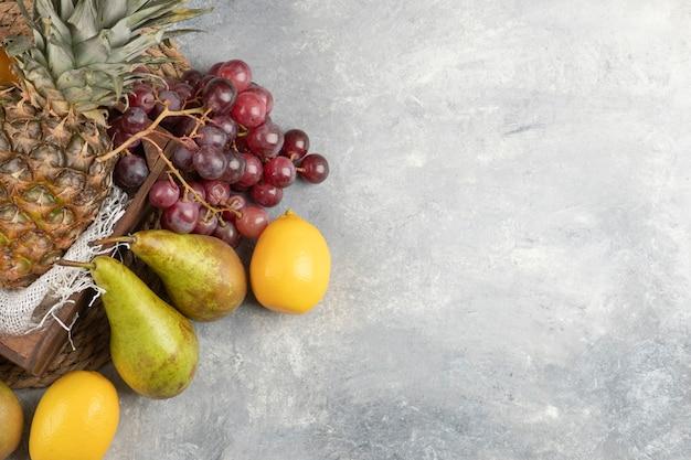 Ananas mûr dans une boîte en bois avec divers fruits frais sur une surface en marbre.