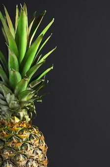 Ananas mûr avec des feuilles vertes sur fond noir.