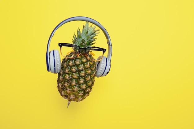 Un ananas mûr frais dans des lunettes portant des écouteurs sans fil sur fond jaune