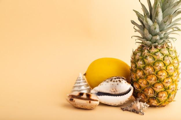 Ananas mûr, melon, coquillages sur fond pastel orange. vue latérale, copiez l'espace. tropical,