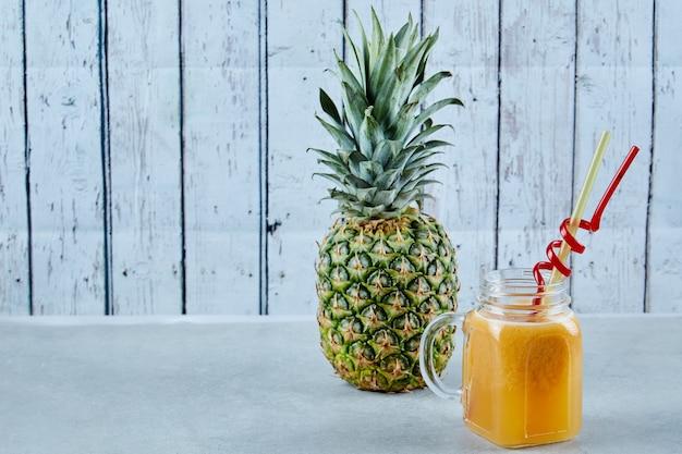 Ananas mûr et un verre de jus sur bleu.