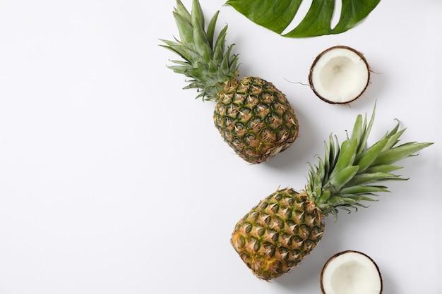 Ananas, noix de coco et feuilles de palmier sur fond blanc, espace pour le texte