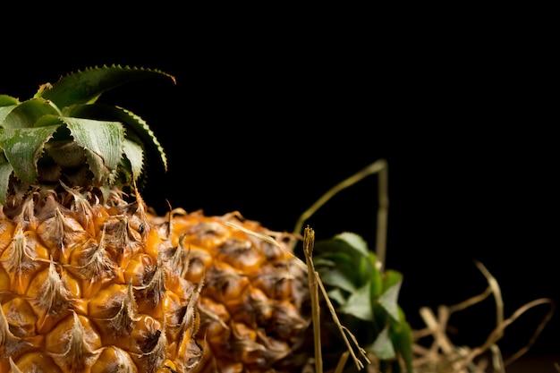 Ananas. paille. fond noir