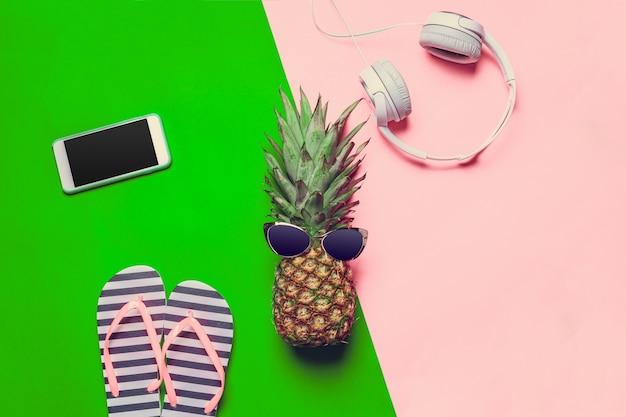 Ananas sur papier de couleur avec fond de lunettes