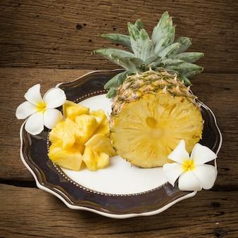 Ananas sur plat demi fleur sur vieux bois
