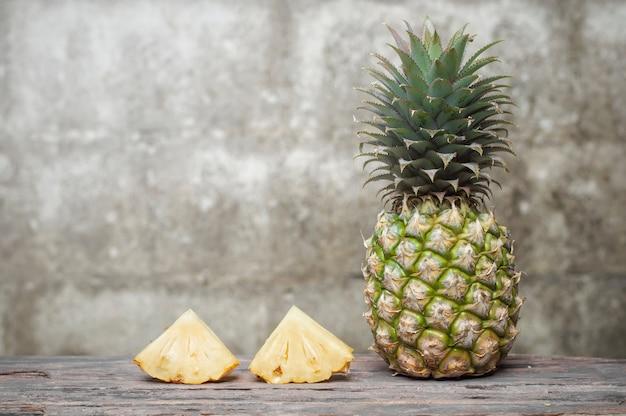 Ananas sur une table en bois avec vieux fond de mur de brique