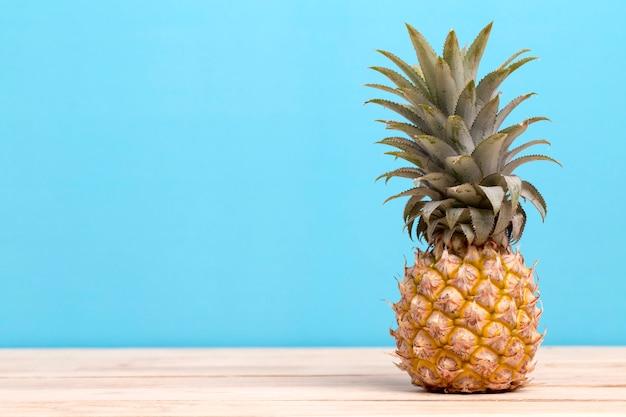 Ananas sur une table isolée sur fond bleu