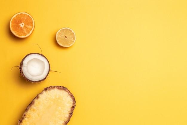 Ananas tropical, oranges, citron et noix de coco sur un fond pastel.