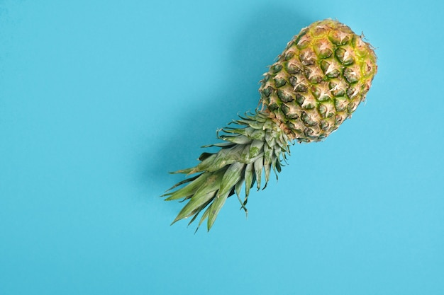 Ananas volant sur fond bleu. concept d'été. copie espace, minimalisme.