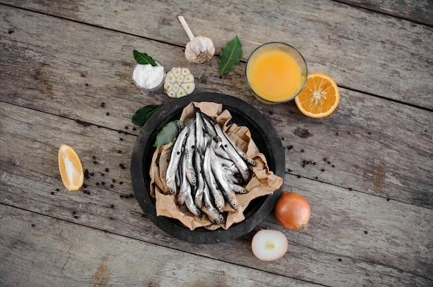 Anchois frais sur plaque sur papier sulfurisé avec jus d'orange frais, ail, oignon et citron autour de la table en bois
