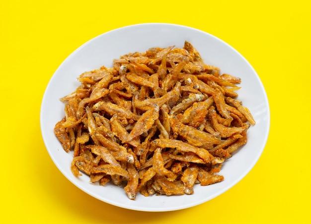 Anchois frits en plaque blanche sur fond jaune.