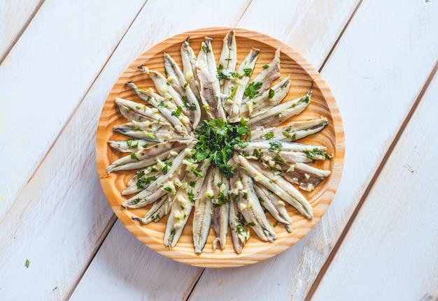 Anchois marinés à l'ail et au persil dans une assiette en bois ronde sur une table en bois blanc. collation espagnole typique.