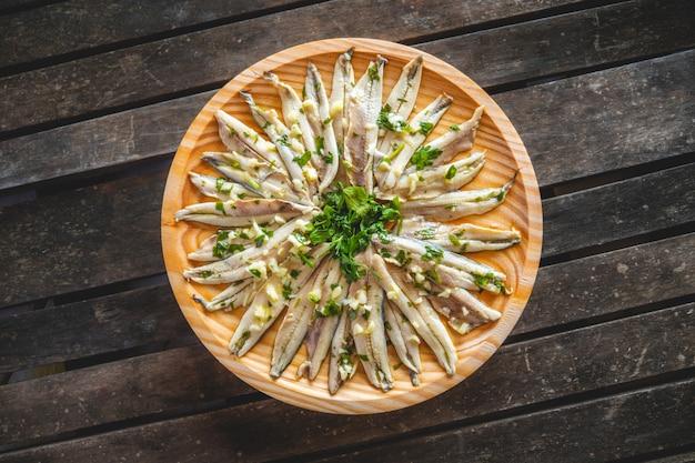 Anchois marinés à l'ail et au persil dans une assiette en bois ronde sur une table en bois sombre. collation espagnole typique.