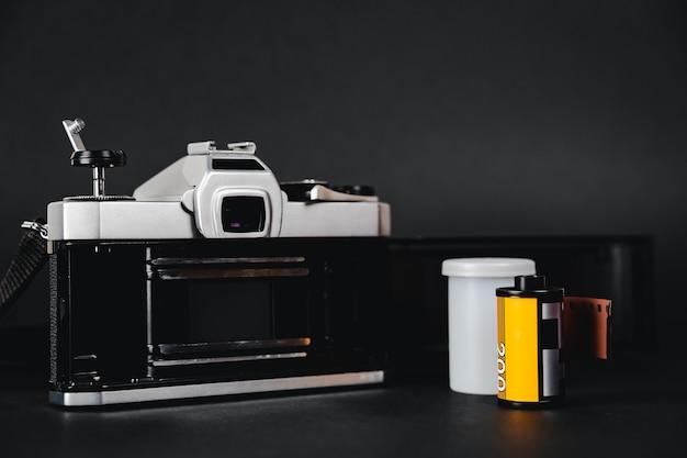 Ancien appareil photo argentique slr et un rouleau de film sur fond noir, concept de photographie.