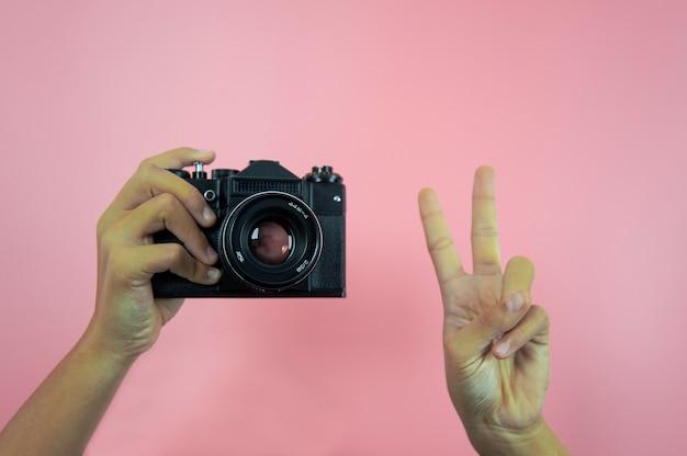 Ancien appareil photo en mains féminines sur fond rose