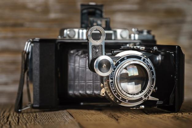 Ancien appareil photo pliant sur une surface en bois rustique texturé.