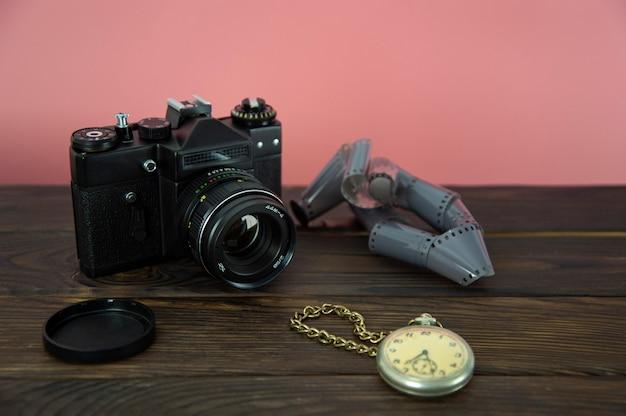 Ancien appareil photo et réveil sur une surface en bois