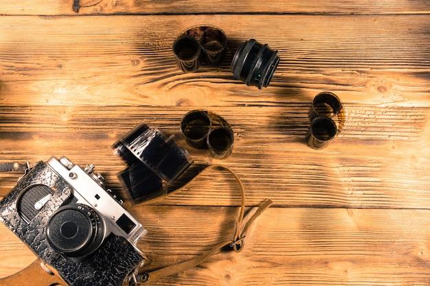 Ancien appareil photo télémétrique et films sur table en bois rustique. vue de dessus