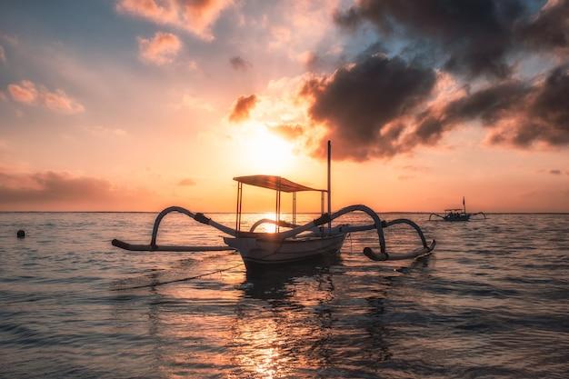 Ancien bateau de pêche traditionnel jukung au bord de la mer au lever du soleil coloré. plage de sanur, bali, indonésie