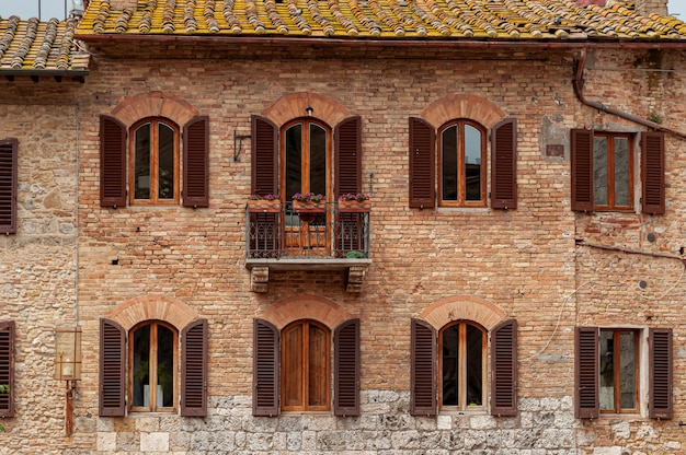 Ancien bâtiment en brique rouge avec volets en bois ouverts sur les fenêtres et le toit de tuiles