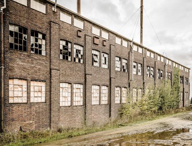 Ancien bâtiment en pierre abandonné avec des fenêtres cassées et une flaque d'eau à l'extérieur