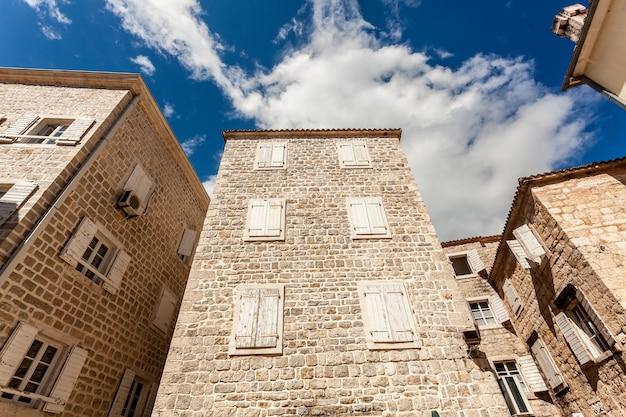 Ancien bâtiment en pierre avec fenêtres fermées aux beaux jours