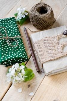 Ancien bloc-notes vintage tricoté en pull beige, écheveau épais de fil, tissu, fleur de poire, crayon allongé sur la table en bois non peinte.