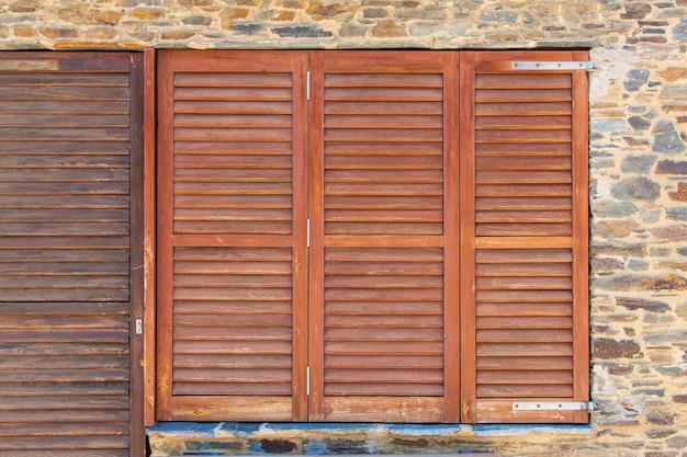 Ancien cadre de fenêtres en bois sur un mur de pierre en espagne