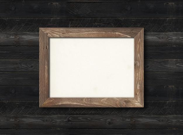 Ancien cadre photo en bois rustique accroché sur un mur en bois noir