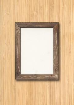 Ancien cadre photo en bois rustique brun accroché sur un mur en bois