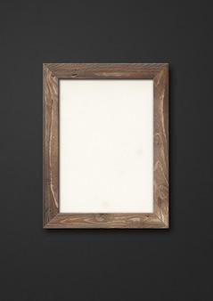 Ancien cadre photo en bois rustique brun accroché sur un mur noir. modèle de maquette vierge