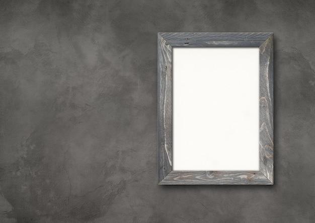 Ancien cadre photo en bois rustique gris accroché sur un mur de béton foncé. bannière horizontale. modèle de maquette vierge